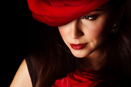 Pictire de femme sexy avec une grande rose rouge chapeau sur la tête isolée sur fond noir, closeup portrait d'une jeune fille élégante avec le bouquet de fleurs, Saint-Valentin, de la beauté et un salon de coiffure, un concept d'élégance