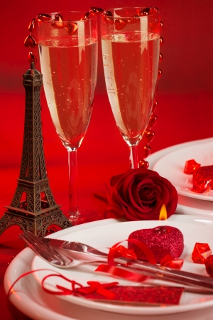 Image of red luxury table setting, white festive plate and two glass of champagne decorated with small Eiffel tower and fresh rose flower, dinner in Paris, honeymoon in France, Valentine day  photo