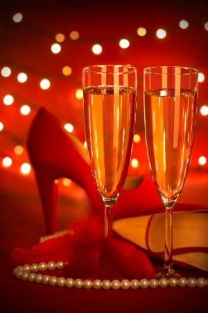 Photo of beautiful red romantic still life, two glass of champagne, shoes on high heels, luxury white pearl beads, fluffy feather, festive lights, holiday presents, Valentine day, love concept photo