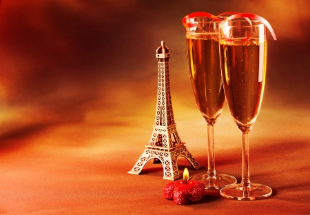 Photo of two wine glass decorated with red ribbon, heart-shaped candle and small Eiffel tower, beverage still life, Valentine day in Paris, dark grange background, love and romance concept photo