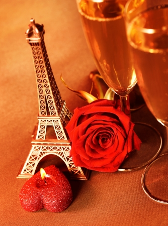 Photo of two glass of champagne on the table in restaurant, festive romantic still life, alcoholic beverage, red rose and candle, wedding day, honeymoon in Paris, travel to France, Valentine day  photo