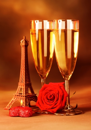 Image of festive romantic still life, alcoholic beverage, two glass with sparkling wine, honeymoon in Paris, travel to France, red fresh rose and heart-shaped candle, Valentine day, love concept photo
