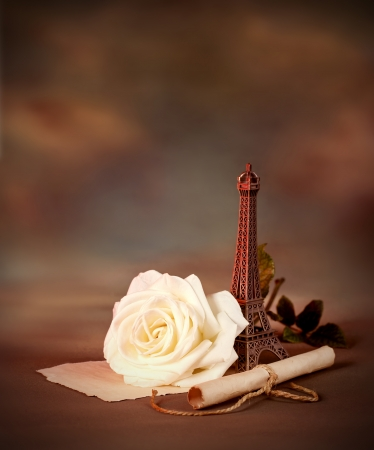 Photo of beautiful romantic still life on dark grunge background, love letter, old paper scroll with romantic message decorated with small Eiffel tower, Valentine day in Paris, honeymoon in France photo