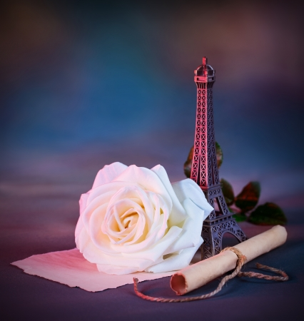 poem: Picture of beautiful retro style still life over blue grunge background, white fresh rose flower, small decorative Eiffel tower, love letter, aged paper scroll with handwriting poem, Valentine day