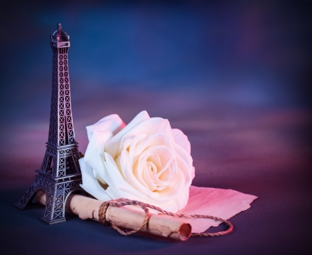 Image of festive greeting card with fresh white rose on the table decorated with small Eiffel tower, vintage photo, wedding in Paris, love letter on parchment, Valentine day in Europe photo