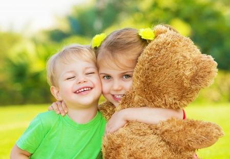 Foto twee schattige kinderen knuffelen buitenshuis, broer en zus plezier op achtertuin in het voorjaar, mooie meisje met schattige jongen spelen met grote zachte beer speelgoed, beste vrienden, gelukkige jeugd begrip