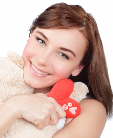Photo of pretty woman hug cute soft toy, closeup portrait of pretty brunette female with teddy bear and red handmade heart isolated on white background, Valentine day, love and happiness concept Stock Photo - 17792612