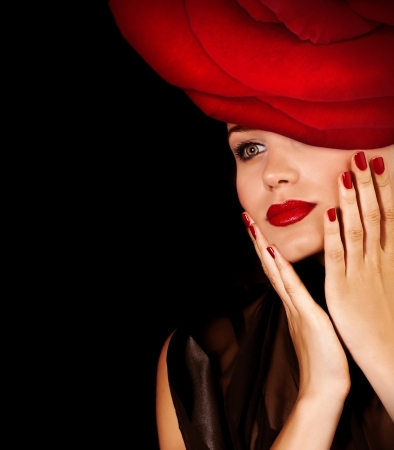 Photo of gorgeous luxury model with festive makeup wearing glamorous floral hat with great red rose isolated on black background, fashionable accessories, sexy female, passion and seduction concept Stock Photo - 17792512