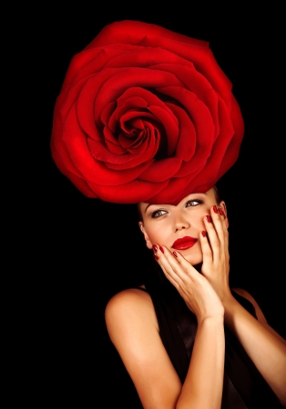Picture of stylish young lady with big red rose on the head isolated on black background, fashionable model wearing glamorous floral hat, Valentine day, luxury lifestyle, vogue and style concept photo