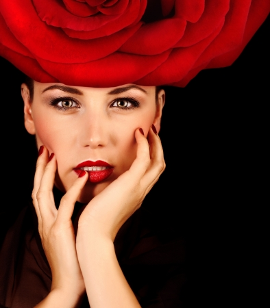 Photo of beautiful sexy woman with red rose hat on the head isolated on black background, closeup portrait of seductive woman with perfect makeup, Valentine day, beauty salon, fashion style photo