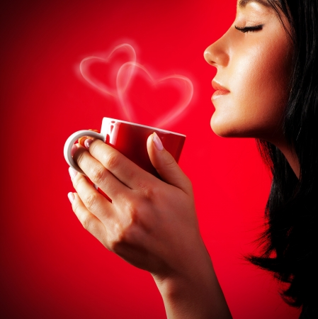 Beautiful lady drinking coffee, brunette enjoy cup of hot chocolate, side view cute girl isolated on red background, portrait of female with morning tea, gorgeous woman holding cappuccino mug photo