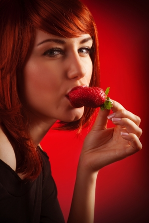 Photo of pretty woman with red hair eating strawberry, closeup portrait of seductive female isolated on red background, sexy girl biting fresh juicy fruit, Valentine day, passion and love concept photo