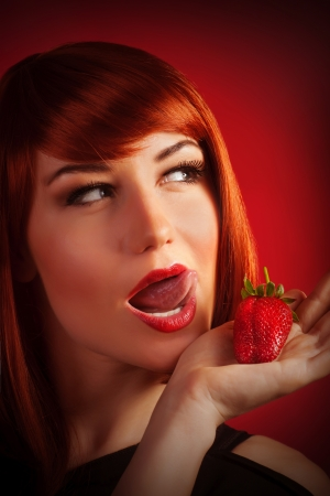 Picture of attractive female with open mouth isolated on red background, sexy red hair woman eating fresh strawberry, healthy lifestyle, fruity diet, Valentine day, pleasure and enjoying concept photo