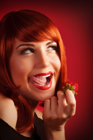 Image of seductive redhead girl holding in hand fresh strawberry, closeup portrait of sexy woman with open mouth eat juicy fruit isolated on red background, Valentine day, passion concept photo