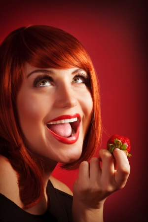 red head woman: Photo of attractive red head woman eat sweet strawberry, closeup portrait of playful girl with open mouth and looking up isolated on red background, healthy lifestyle, pleasure and seduction concept