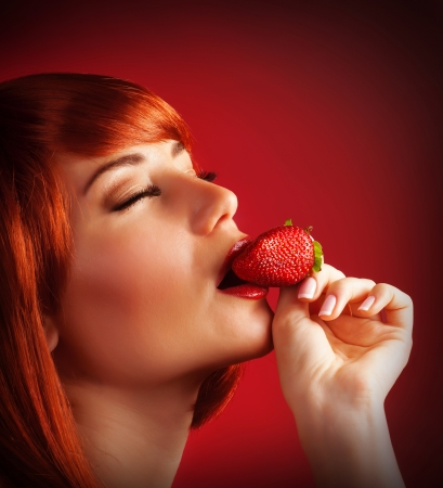 Photo of seductive female eating strawberry, closeup portrait of redhead sensual woman biting juicy fruit isolated on red background, fruity diet, tasty dessert, Valentine day,  pleasure concept