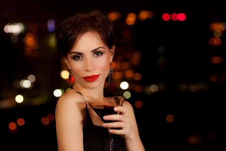 Photo of a beautiful woman having martini in outdoor restaurant, celebration party, city nightlife lifestyle, glamorous lady with drink, female enjoying cocktail  photo