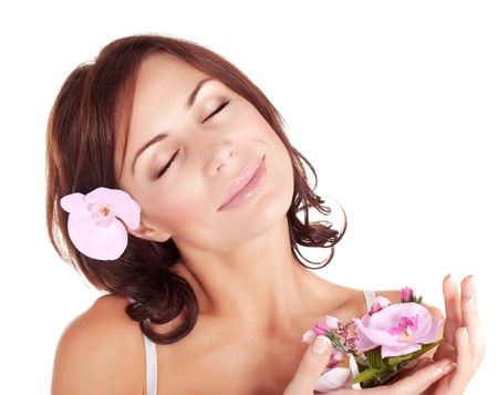 Photo of cute brunette girl with closed eyes enjoying dayspa, portrait of pretty young lady with pink orchid flower isolated on white background, luxury spa salon, natural treatment, beauty concept photo