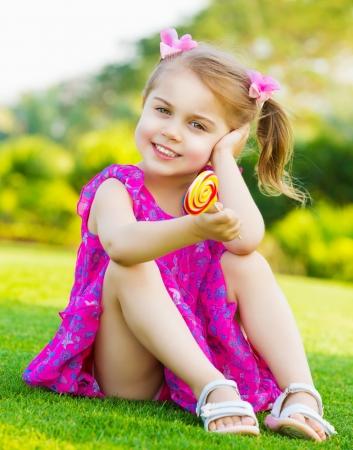 petite fille avec robe: mignonne petite fille assise sur l'herbe verte sur cour et tenant dans la main coloré sucette