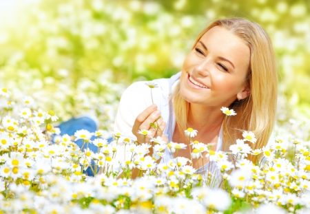 lying down: Image of sweet girl lying down on daisy glade and enjoying warm sun light, beautiful woman holding in hand little camomile flower, recreation on floral field, relaxation in rural place, spring holiday Stock Photo