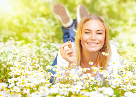 lying down: cute blond young lady enjoy beautiful spring natureconcept