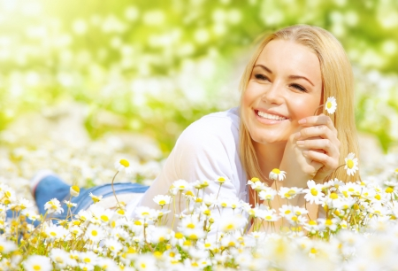 pretty woman lying down on chamomile field, happy female holding in hand beautiful white flower Stock Photo