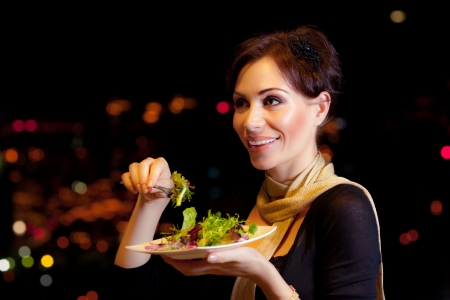dine: Image of beautiful female eating salad on the party, night lifestyle, attractive woman have dinner in restaurant outdoor, girl wearing dress holding in hand plate with meal, holiday celebration