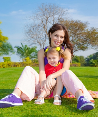 Photo of young mother with cute little daughter sitting down on green grass field in park, beautiful woman with small pretty girl having fun outdoors in spring, happy family on picnic, love concept photo