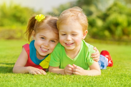 girl lying: Image of two happy children having fun in the park, brother and sister lying down on green grass, best friends playing outdoors in spring, adorable little girl with cute boy enjoying springtime nature