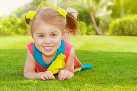 Picture of cute little girl lying down on green grass in park, cheerful child resting on the field on backyard, pretty kid having fun outdoors in springtime, spring nature, sunny day, happy childhood photo