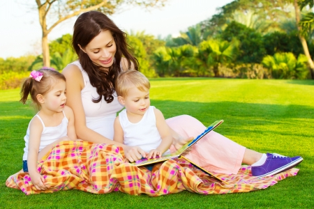 persona leyendo: Foto de la madre joven con dos niños lindos lectura libro al aire libre en primavera, mamá feliz enseñando a sus hijos en el parque, guarderías, mujer hermosa con el hijo y la hija que se divierten en patio trasero Foto de archivo