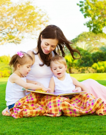 Picture of beautiful woman with daughter and son sitting down on green grass field and read fairytale, cheerful mother and two pretty kids enjoying book on backyard in spring, happy family concept photo