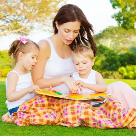 Image of cute young female with two little children read book outdoors, brother and sister with mother learning in the park in spring time, preschool education, day care, happy family concept photo