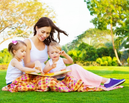 family grass: Picture of beautiful woman with daughter and son sitting down on green grass field and read fairytale, cute female with two little children enjoying book outdoors, preschool education, happy family Stock Photo