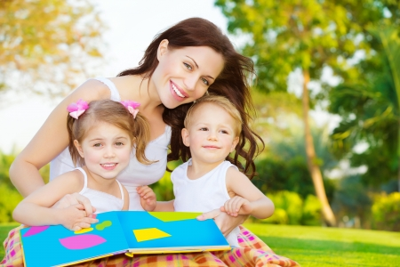 Image of cute young female with two little children read book outdoors, cheerful mother and two pretty kids sitting down on  backyard and enjoying spring nature, daycare, loving family concept photo