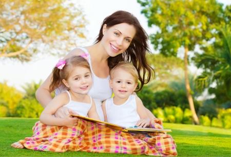 bambini seduti: Foto di attraente donna bruna con due piccoli bambini intelligenti seduto sul campo verde nel parco in primavera e di leggere il libro, la madre con la figlia e il figlio godere da favola, il concetto di famiglia felice