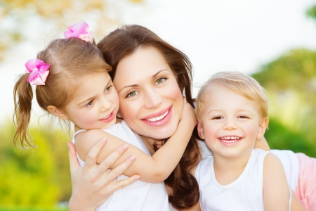 girl woman: Picture of young mother hugging two little children Stock Photo