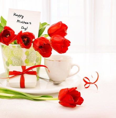 Picture of beautiful tulips pot with gift box and cup of tea on the table at home photo