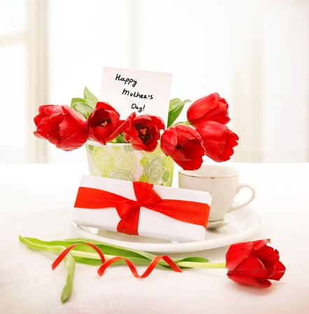 Image of fresh red tulips bouquet in beautiful vase with greeting postcard on the table, little white giftbox with ribbon, cup with morning coffee, breakfast for mommy, happy mothers day concept photo