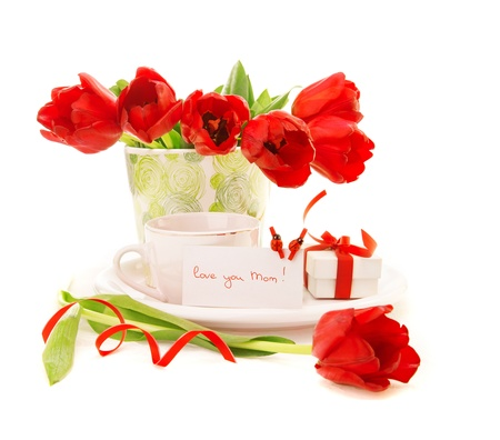 tulips in vase: fresh red tulip flowers in vase and cup of coffee isolated on white background