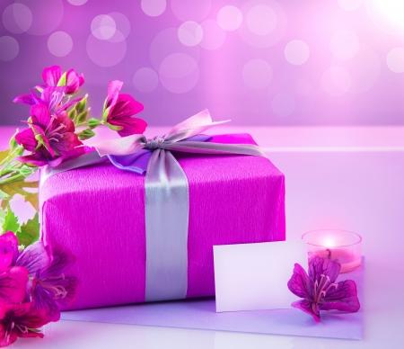 birthday flowers: Foto van roze luxe geschenkdoos met boeket van prachtige bloemen, romantische kaarsen en postkaart met tekst ruimte op de tafel, feestelijk stilleven, onscherpe achtergrond, gelukkig moeders dag, lente seizoen Stockfoto