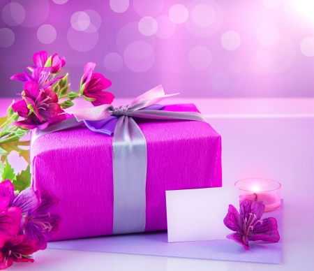 Picture of pink luxury gift box with bouquet of beautiful flowers, romantic candle and postcard with text space on the table, festive still life, blurry background, happy mothers day, spring season photo