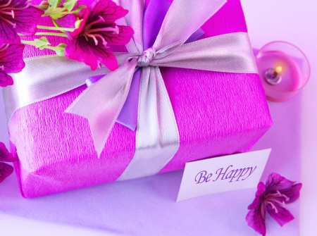 Picture of big pink present box, candle and purple flowers on the table at home photo