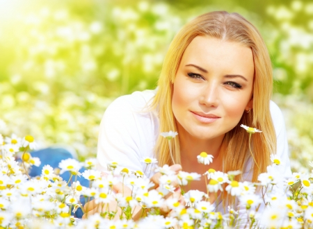 Picture of beautiful female lying down on chamomile meadow in sunny day, attractive young lady resting on white flowers field, rural place, relaxation outside, spring holiday and vacation concept Stock Photo
