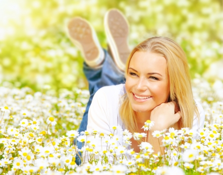 sun down: Picture of pretty woman lying down on chamomile field, happy female enjoying spring nature, cheerful girl resting on daisy meadow, beautiful small white flowers, relaxation outdoor in springtime