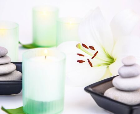 Photo of spa still life, white lily flower, candles, pebble stones, alternative treatment, enjoying dayspa, aroma therapy, aromatic massage, body care, essential oil, luxury spa salon, harmony concept photo