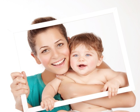 cute little girls: Photo of attractive female holding in hands cute baby boy, closeup portrait of young mother hug her little son, white frame decorations, studio shot, happy family, child care and love concept Stock Photo