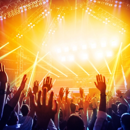 rock concert: Immagine di un sacco di persone che godono di notte perfomance del famoso dj, grande folla di danza giovanile con alzato le mani sul concerto rock, party in discoteca, luce di colore giallo brillante da stadio, vita notturna