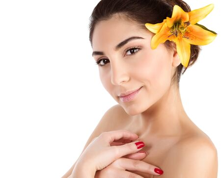 hair treatment: Image of lovely female with fresh yellow lily flower in black hair isolated on white background, young lady relaxed in luxury spa salon, beauty treatment, body care, herbal therapy, wellness concept