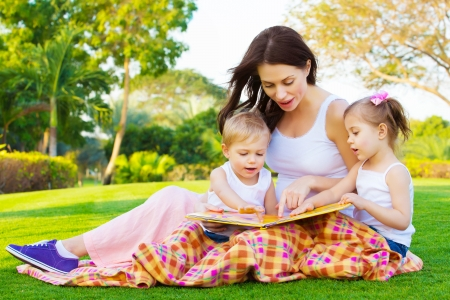 sitting on the ground: Photo of young brunette woman teaching two sweet kids, cheerful mother with cute daughter and lovely son read interesting fairytale, children enjoying book on backyard in daycare, spring season